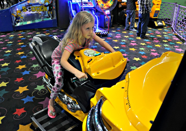 Kaylee playing a motorcycle game at John's Incredible Pizza in Buena Park, CA