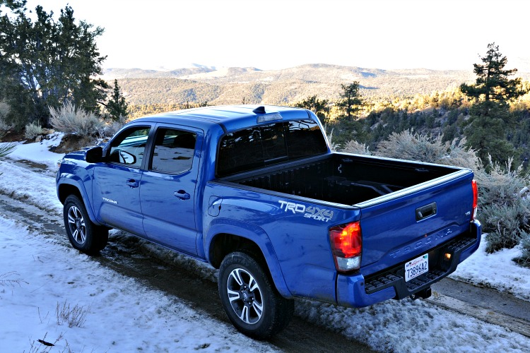 View of blue Toyota Tacoma from the hill above