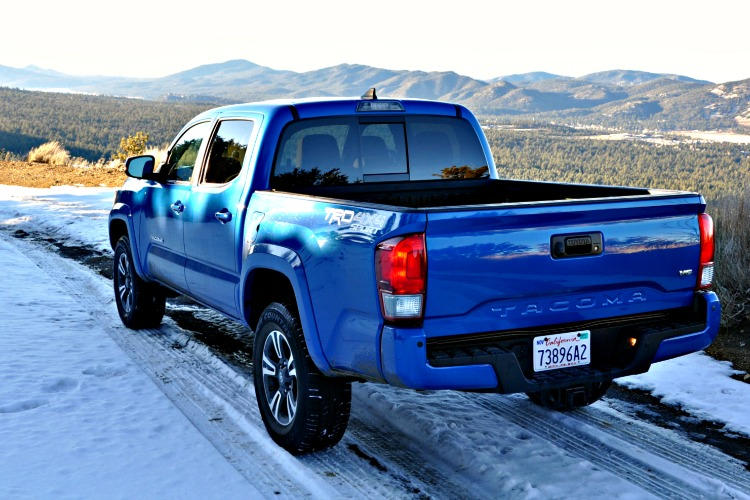 Rear view of blue Toyota Tacoma driving on snowy mountain trails