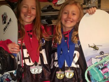 Zoë and Kaylee holding their snowboards in Mammoth