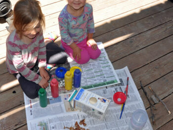The girls working on their milk carton bird house