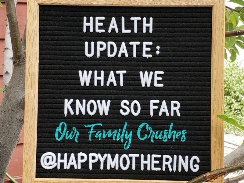"Sign that reads, ""Health Update: What We Know So Far; Our Family Crushes; @HappyMothering"""
