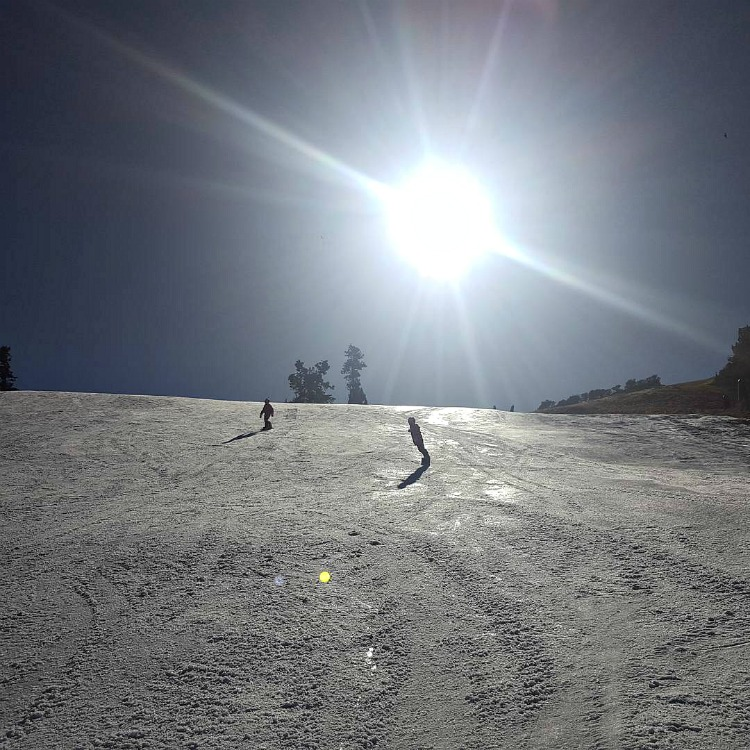 Zoe and Kaylee snowboarding at Bear Mountain with the sun in the background