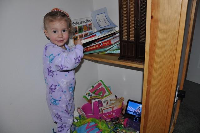 Zoë organizing her books in the closet