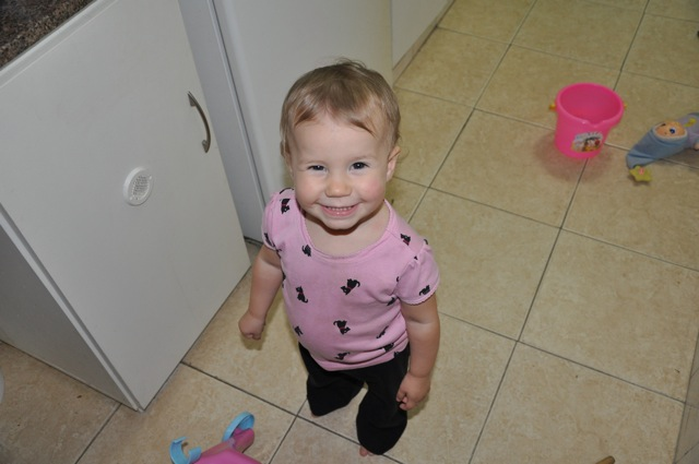 Zoë smiling at the camera as a toddler