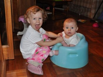 Zoë playing with Kaylee in her Bumbo seat