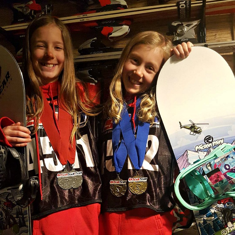 Zoe and Kaylee with their snowboards and medals