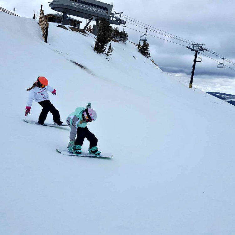 Zoe and Kaylee doing tailpresses on their snowboards