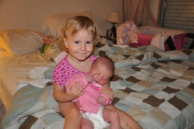 Zoë holding Kaylee on our bed