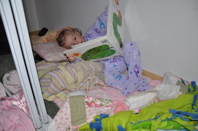 Zoë reading a book in the closet