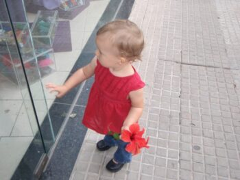 Zoë holding a red flower looking in a window