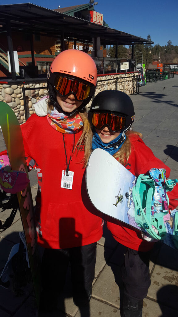Zoë and Kaylee with their snowboards at Bear Mountain on the deck