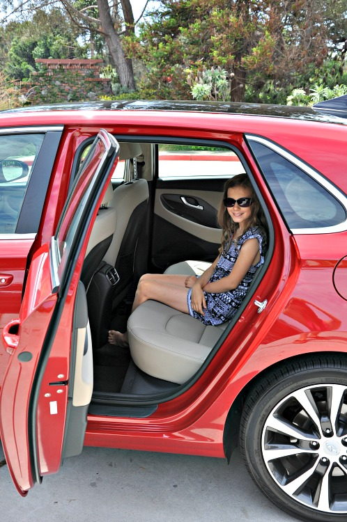 Zoë sitting in the back seat of a red Hyundai Elantra GT