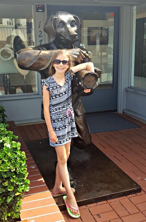 Zoë standing with a dog statue in La Jolla, CA