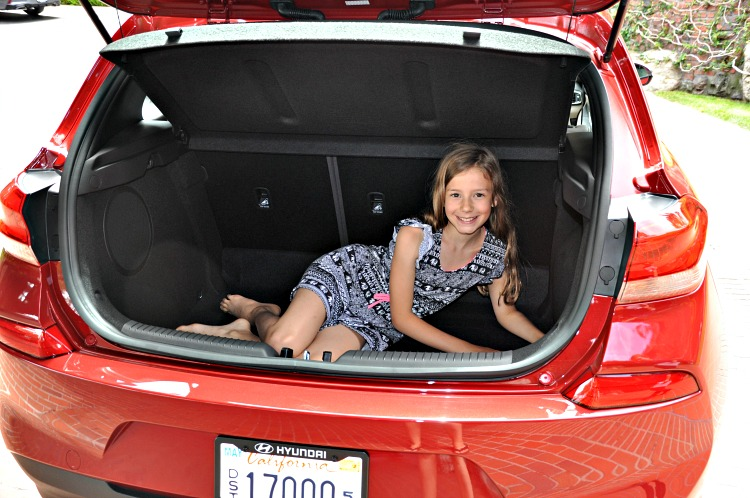Zoë showing how big the trunk is in the Hyundai Elantra GT by sitting in it