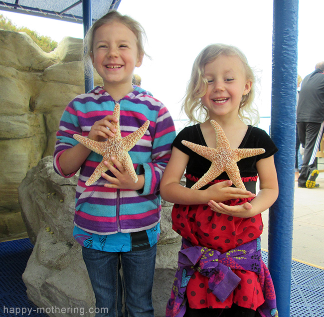 Zoë and Kaylee holding star fish at Birch Aquarium La Jolla