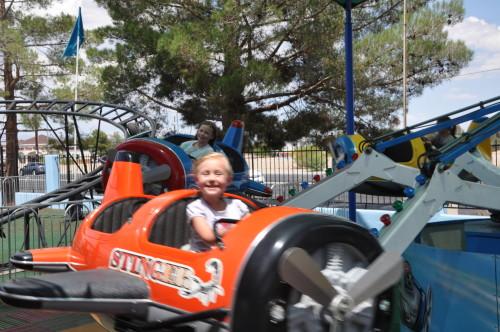 Kaylee in an orange airplane ride at Las Vegas Mini Gran Prix