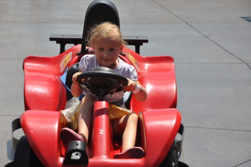 Kaylee driving a red car around the track