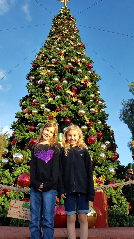 Zoë and Kaylee in front of the Christmas tree during the day at Knott's Merry Farm