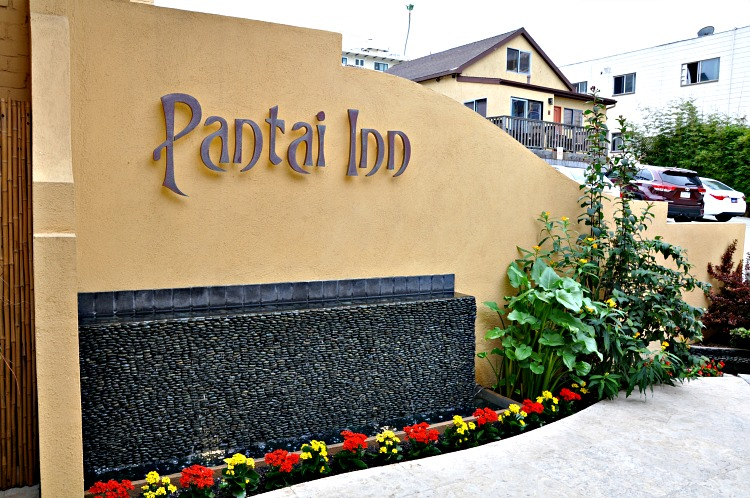 Pantai Inn sign with water feature and greenery