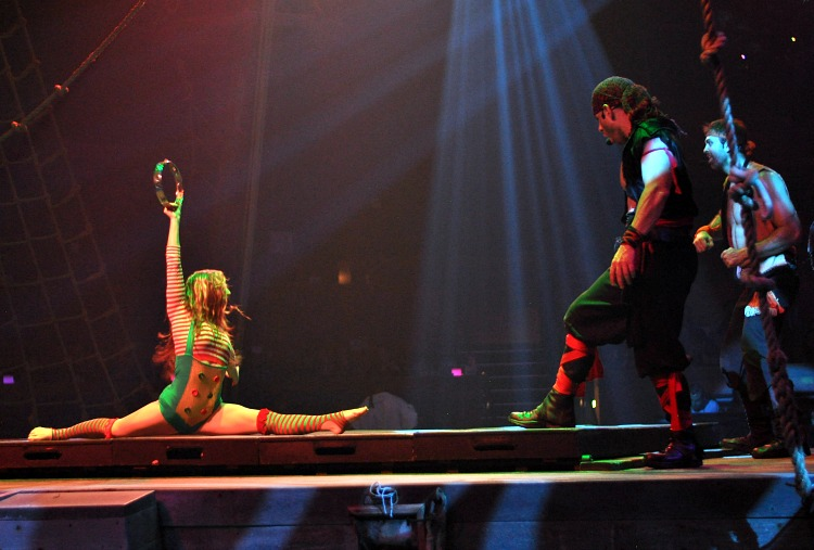 Acrobat doing the splits by a pirate on stage