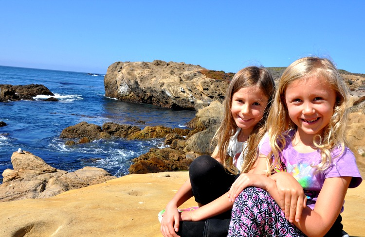 Zoë and Kaylee sitting on the cliffs at Point Lobos State Reserve on our family trip