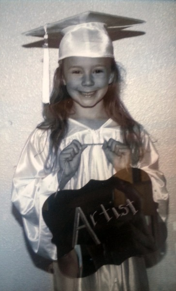 Zoë wearing a graduation outfit and holding a sign saying artist