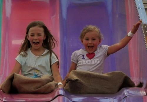 Girls smiling on pink and purple slides at Las Vegas Mini Gran Prix