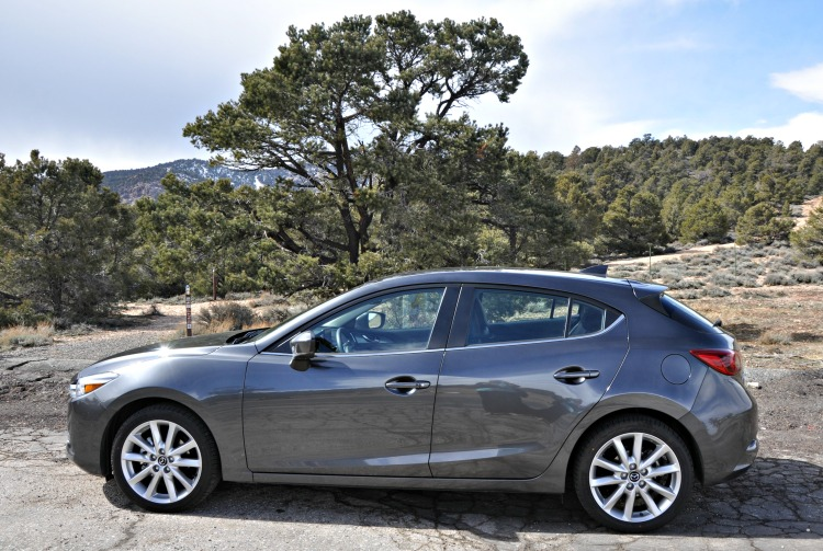 Side view of gray Mazda3 with nature in the background