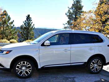 Side of the Mitsubishi Outlander with mountains and trees in the background