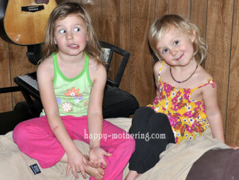Zoë and Kaylee sitting on the brown couch making goofy faces for the camera