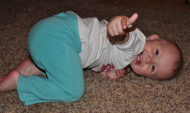 Toddler Kaylee pointing at the camera from a silly pose on the ground