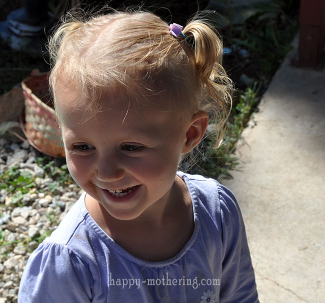 Kaylee smiling outside with pigtails
