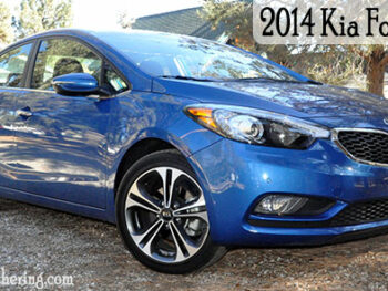 Blue Kia Fore in rock covered driveway