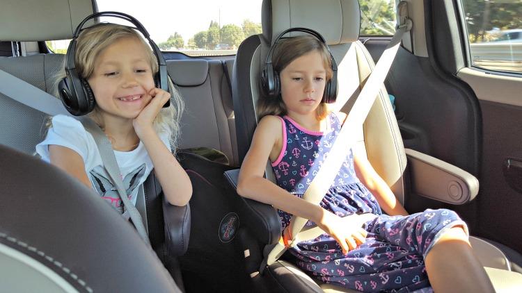 Zoë and Kaylee wearing headphones and watching TV in the Kia Sedona Minivan
