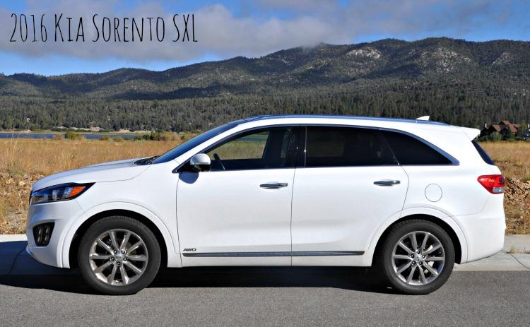 White Kia Sorento with the mountains and lake in the background