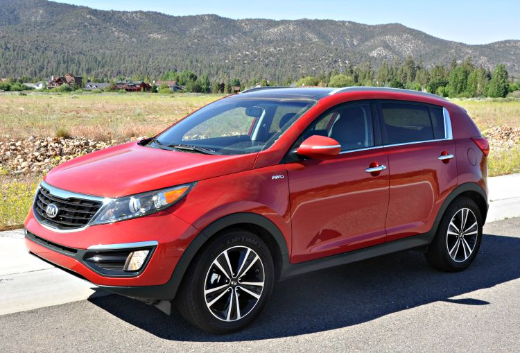 Red Kia Sportage with grassy fields behind it