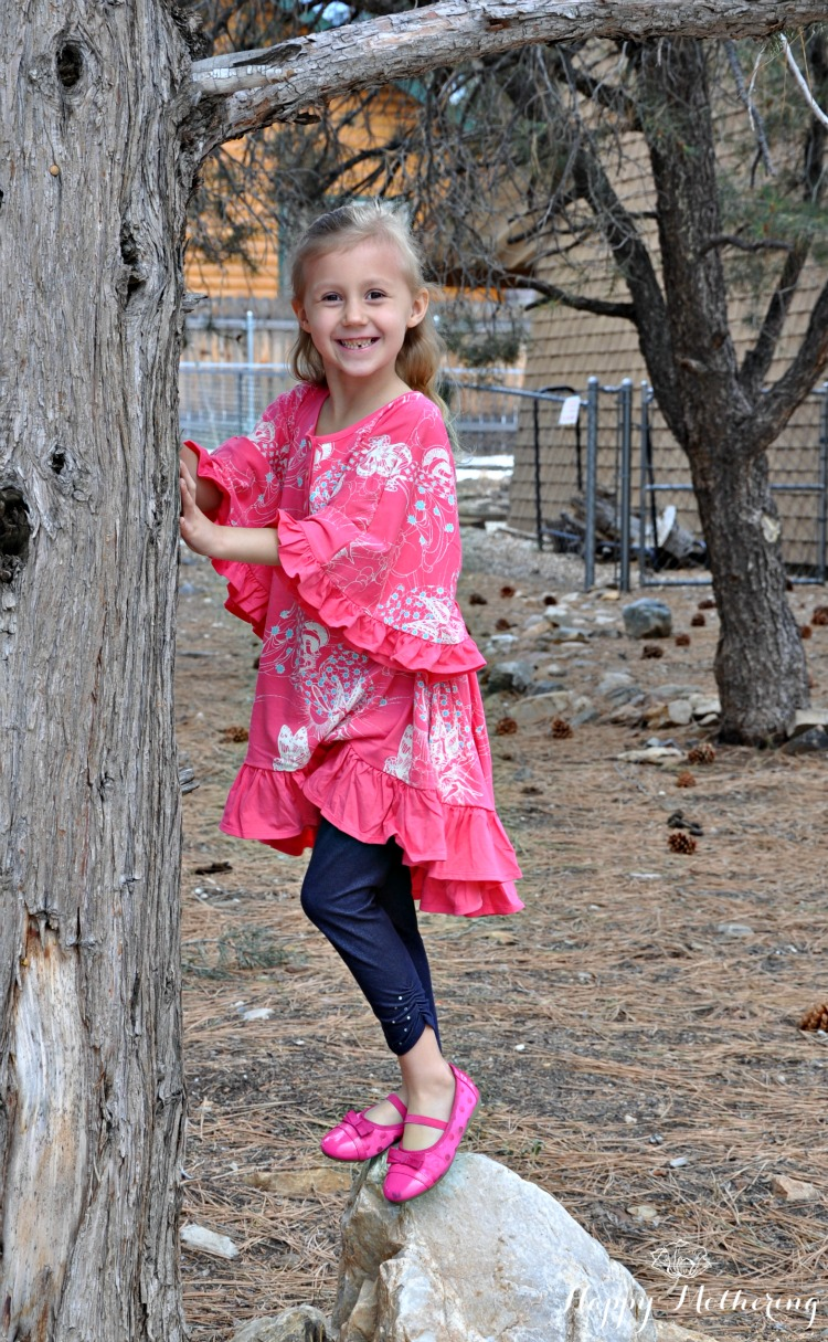 Kaylee under a tree on a rock wearing Little Skye Boutique clothes