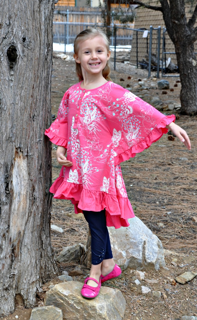 Kaylee doing a ballet pose under a tree in her Little Skye Boutique top