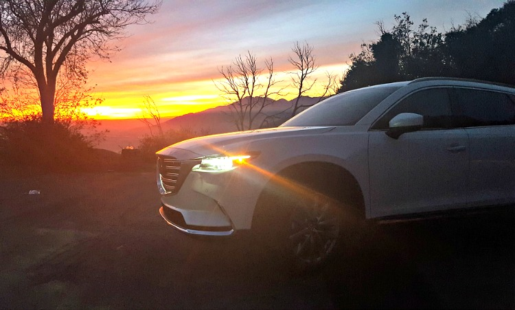 Mazda CX-9 at sunset with mountains and trees in the background