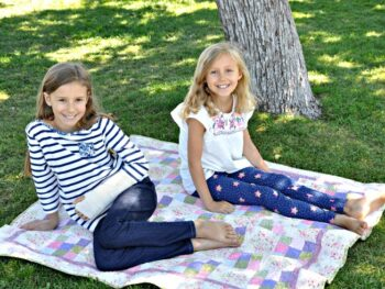 Zoë and Kaylee sitting on a quilt under a tree at the park