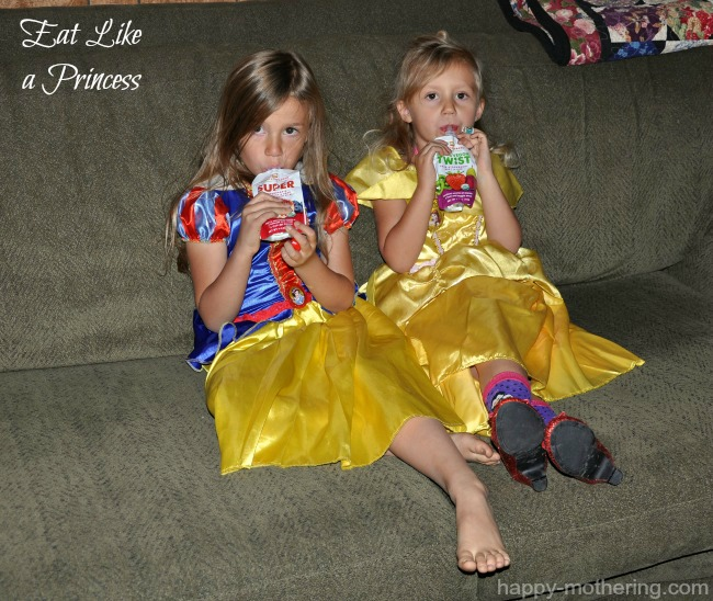 Zoë and Kaylee eating snacks on the couch in their Snow White and Belle costumes