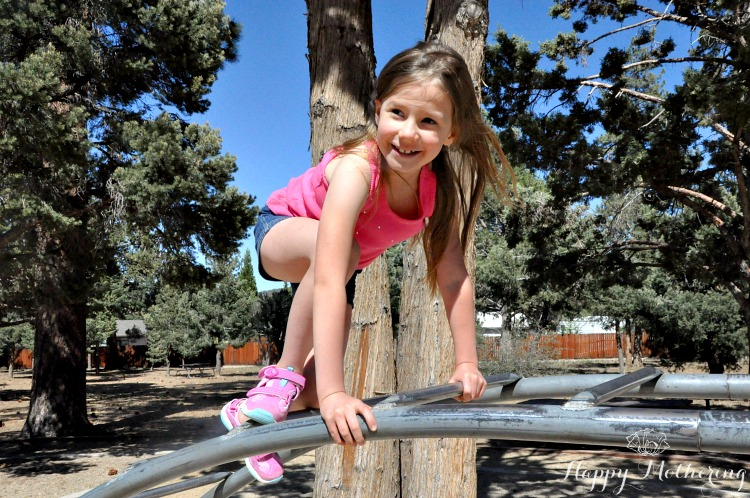 Zoë climbing on the rainbow bars at the park