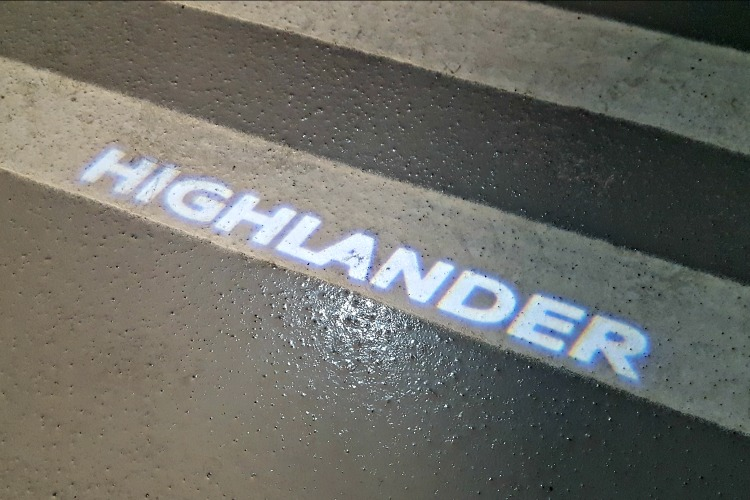 """Highlander"" written in lights on the ground from the vehicle"