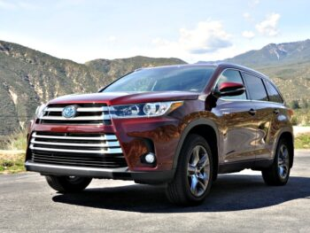 Front angle of Toyota Highlander Hybrid with green mountains in the background