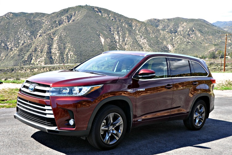 Side of red Toyota Highlander Hybrid in front of mountains