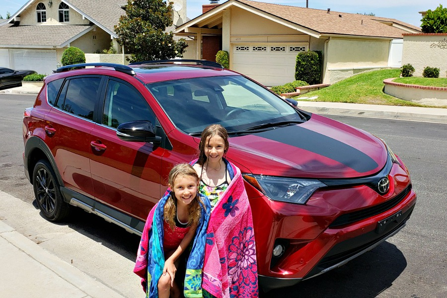 Zoë and Kaylee in front of the red Toyota RAV4 we reviewed