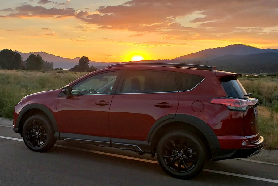 Red Toyota RAV4 at sunset with mountain in the background